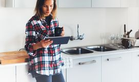 Hipster girl using tablet technology and drink coffee in kitchen, girl person holding computer on background interior cuisine, fem. Ale hands texting message on royalty free stock images