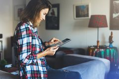 Hipster girl using tablet technology in home atmosphere, girl person holding computer with blank screen on background bokeh royalty free stock photos