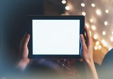Hipster girl using tablet technology in home atmosphere, person holding computer on background glow bokeh Christmas illimination. Female hands texting on relax stock image