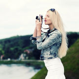 Hipster girl with vintage camera. Modern hipster girl photographed vintage camera outdoors. Lifestyle outdoor portrait Royalty Free Stock Photo