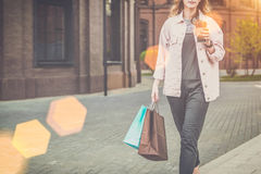Young woman in glasses is walking along city street, carrying shopping bag and holding cup of coffee. Stock Images