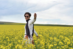 Hipster girl walking through a canola field Stock Images