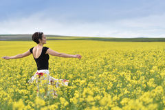 Hipster girl walking through a canola field Royalty Free Stock Photography