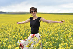 Hipster girl walking through a canola field. Freedom concept Royalty Free Stock Photography