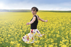 Hipster girl walking through a canola field. Freedom concept Stock Image
