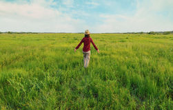 Hipster girl walking on summer meadow. Unrecognizable hipster girl in straw hat walking on summer meadow, rear view. Concept of happiness and carefree Stock Photos
