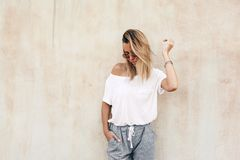 Woman in white t-shirt on beige background. Hipster girl wearing blank white t-shirt and grey pants posing against street wall, blank mockup for tshirt print royalty free stock photos