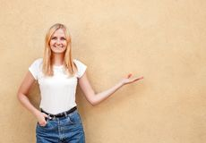 Hipster girl wearing blank white t-shirt and jeans posing against rough street wall, minimalist urban clothing style royalty free stock images