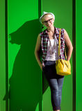 Hipster girl with yellow bag leaning against green wall Stock Photos