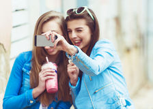 Hipster girlfriends taking a selfie in urban city Stock Photos