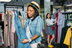 Hipster girls choosing clothes in shopping mall, boutique shopping concept Stock Images