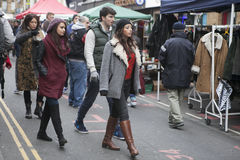 The hipster girls dressed in cool Londoner style walking in Brick lane, a street popular among young trendy people Royalty Free Stock Image