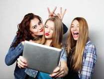 Hipster girls friends taking selfie with digital tablet. Life style, tehnology and people concept: hipster girls friends taking selfie with digital tablet Stock Images