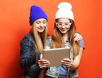 Hipster girls friends taking selfie with digital tablet, studio Royalty Free Stock Photos