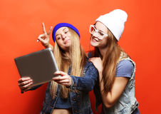 Hipster girls friends taking selfie with digital tablet, studio. Two hipster girls friends taking selfie with digital tablet, studio shot over orange  background Royalty Free Stock Images