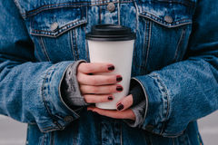 Hipster girls hands holding a hot drink. Hands hipster girl in a blue denim jacket holding a hot drink Royalty Free Stock Photos