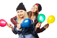 Hipster girls smiling and holding colored balloons Stock Photo