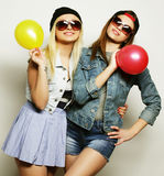 Hipster girls smiling and holding colored balloons Stock Image
