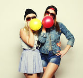 Hipster girls smiling and holding colored balloons Royalty Free Stock Photography