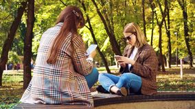 Hipster girls surfing social media on smartphones outdoors. Hipster girls sitting face to face on bench in sunny park and surfing internet in smartphones. Pretty stock footage