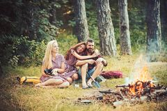 Hipster and girls in vintage dresses smile at bonfire. Love triangle and relations. Happy friends at campfire. Bearded. Men and women relax in forest. Camping stock images