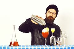 Hipster and glasses of alcoholic beverage, cocktails, shot or shaker. Bearded man, long beard. Brutal caucasian hipster with moustache in rock black style royalty free stock images