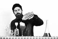 Hipster and glasses of alcoholic beverage, cocktails, shot or shaker. Bearded man, long beard. Brutal caucasian hipster with moustache in rock black style stock image