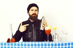 Hipster and glasses of alcoholic beverage, cocktails, shot or shaker. Bearded man, long beard. Brutal caucasian hipster with moustache in rock black style Stock Images