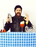 Hipster and glasses of alcoholic beverage, cocktails, shot or shaker. Bearded man, long beard. Brutal caucasian hipster with moustache in rock black style royalty free stock image