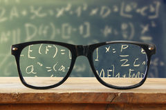 Hipster glasses on a wooden rustic table in front blackboard with math formulas and calculation. vintage filtered Royalty Free Stock Images