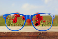 Hipster glasses on a wooden rustic table in front of the field of red poppies. vintage filtered Stock Photo
