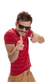 Hipster gunner. Happy, handsome young man with hipster sunglasses, smiles and playfully points his fingers like guns, isolated on white background Royalty Free Stock Image