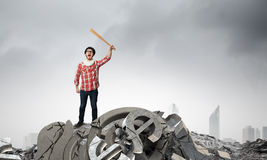 Hipster guy with bat. Young man with baseball bat in anger breaking currency sign Royalty Free Stock Image
