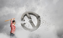 Hipster guy with bat. Young man with baseball bat in anger breaking prohibition sign Royalty Free Stock Image
