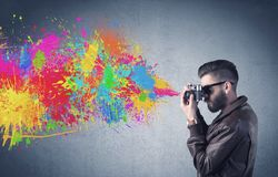 Hipster guy with camera and paint splash stock photos