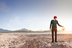 Make your income grow. Mixed media. Hipster guy in desert with metal can. Mixed media Stock Images
