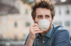 Hipster guy drinking a coffee. Hipster guy having a cappuccino at the bar, he is pensive and looking away Stock Photos