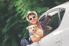 Fashionable guy with his dog out of car window. Hipster guy holding his dog pet out of car window. On the road travel summer vacation concept stock image