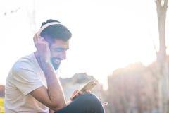 Hipster Guy Listening Music Outdoors stock afbeeldingen