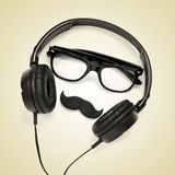 Hipster guy. A pair of glasses, a mustache and a pair of headphones on a beige background, depicting a hipster guy stock photos