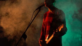 Hipster guy plays guitar and sings on stage in smoke. Slow motion. Music, Sound, Band, Concept stock footage