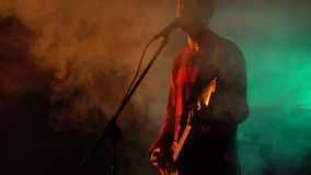 Hipster guy plays guitar on stage in smoke. stock footage