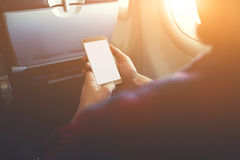 Hipster guy is reading electronic book on cell telephone during flying in plane Stock Photography