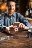 Hipster guy at the restaurant using a mobile phone. Cheerful hipster guy at the restaurant using a mobile phone, hands close up Stock Photos