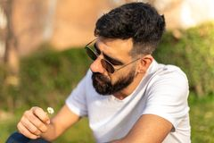 Hipster Guy Sitting Outdoors Holding a Flower stock photography