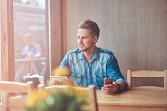 Hipster guy with a stylish haircut and beard sits at a table in a roadside cafe, holds a tablet and smartphone. Handsome hipster guy with a stylish haircut and Stock Photos