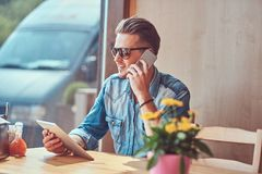 Hipster guy with a stylish haircut and beard sits at a table in a roadside cafe, talking on the phone and holds a tablet. Handsome hipster guy with a stylish Royalty Free Stock Image