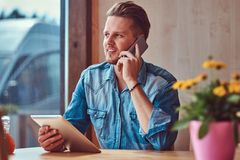 Hipster guy with a stylish haircut and beard sits at a table in a roadside cafe, talking on the phone and holds a tablet stock photo