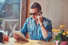 Hipster guy with a stylish haircut and beard sits at a table in a roadside cafe, talking on the phone and holds a tablet. Handsome hipster guy with a stylish Royalty Free Stock Photo