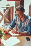 Hipster guy with a stylish haircut and beard sits at a table in a roadside cafe, using a tablet computer. Handsome hipster guy with a stylish haircut and beard Royalty Free Stock Photography